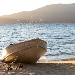 small boat docked on the beach at sunset