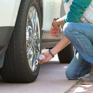 Man kneeling to check tire pressure on white car