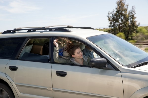Family riding in car with woman's hand out the window