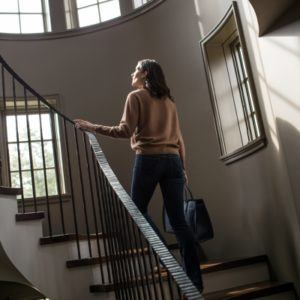 A woman walking up the stairs inside a house