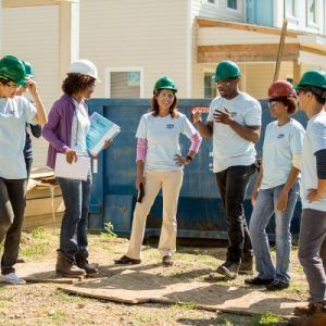 teen volunteers with hardhats in front of house