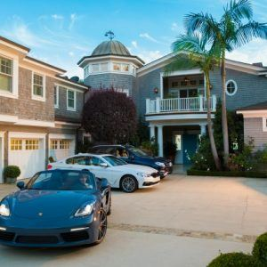Luxury sports cars in driveway of large house