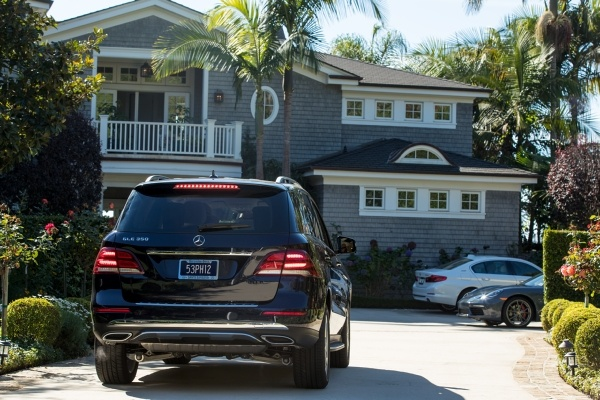 Black SUV in driveway in front of large house