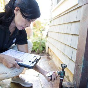 woman holding clipboard and checking water pressure from a spigot