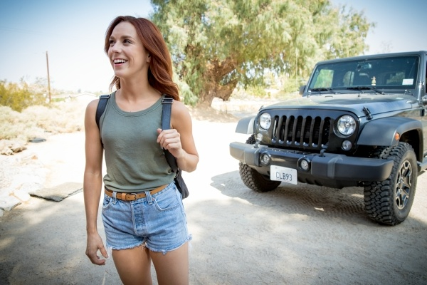 Woman with backpack stands in front of Jeep