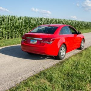 red car driving by cornfield
