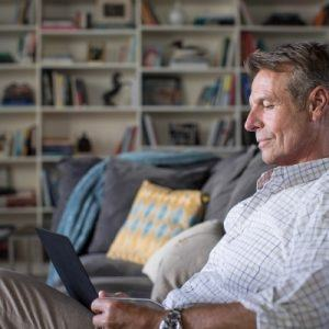 man sitting on couch looking at laptop