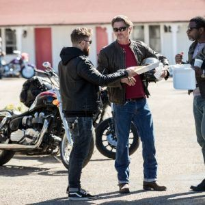 Man holds helmet and talks to another man with motorcycles in background