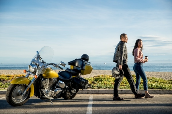 man and woman beside a yellow motorcycle