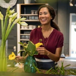 Woman arranging flowers while smiling and laughing