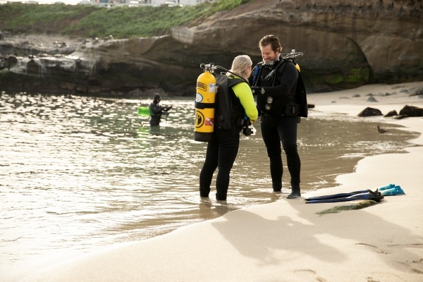 two people getting ready to scuba dive