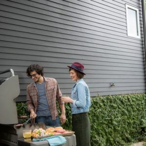 man and woman tending to a grill