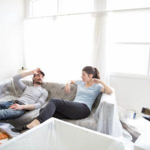 couple sitting on couch after painting house