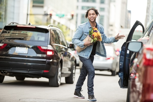 Man Carrying Bouquet Of Flowers And Walking Across Street