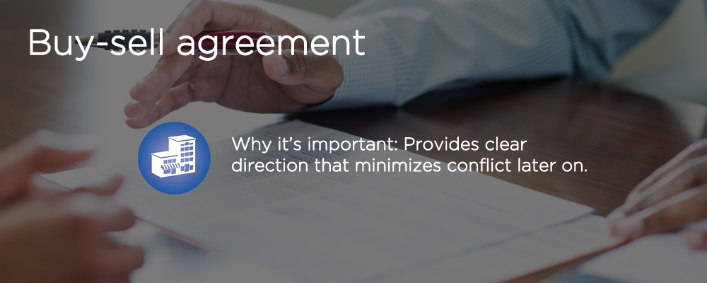 a hand over a document with text 'buy-sell agreement'