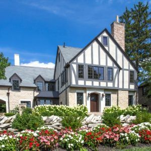 exterior photo of tudor style house with flowers and shrubs