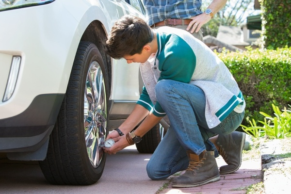 Man checking tire pressure on car