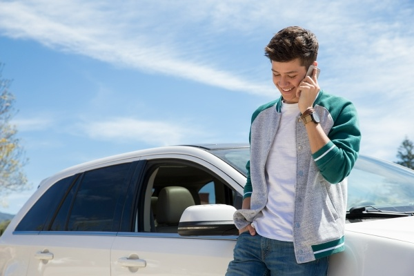 Young man standing beside car talking on cell phone