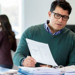 Man with glasses reviewing financial document