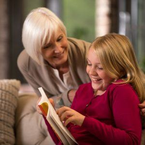 woman reading a book with her granddaughter