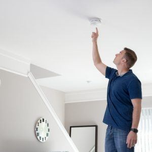 Man with space heater checking smoke alarm
