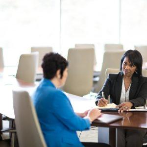 two businesswomen seated at a conference table