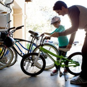father and child putting bikes in the garage