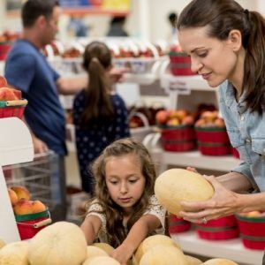 Mother and daughter examining produce at grocery store