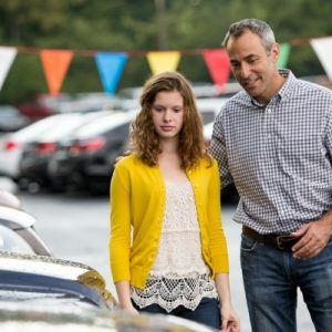 Young woman and father at a car lot