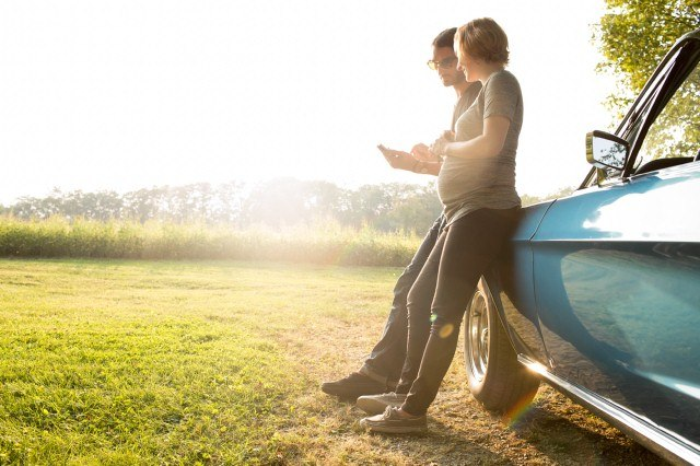 Pregnant woman and man leaning on car
