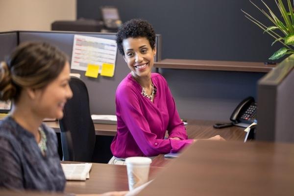 women smiling at their desks