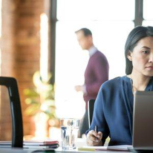 asian woman working in an open concept office