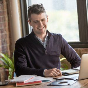 Young man in a home office setting smiling at his laptop