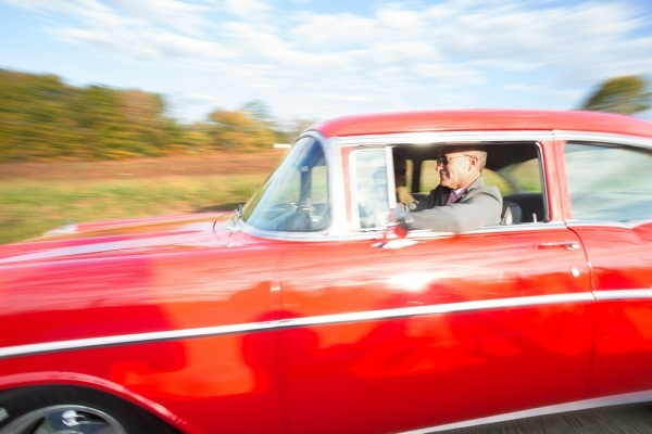 man driving red muscle car