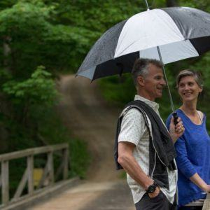 Man and woman standing under umbrella on bridge
