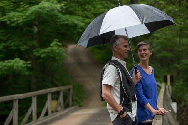 Man and woman standing under umbrella on bridge