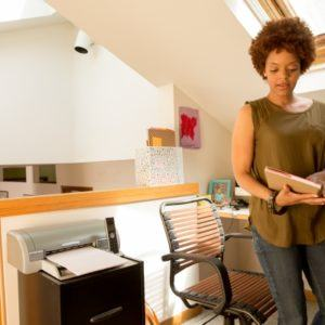 woman standing and reading files in home office