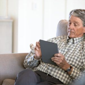 man looking at ipad on couch