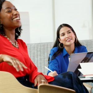 two women laughing while working at desk