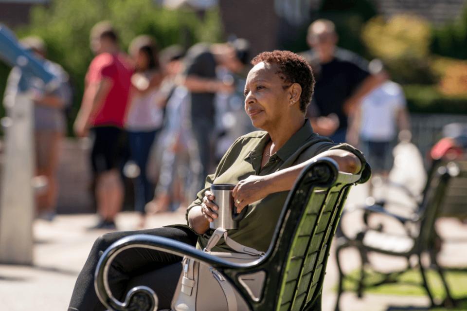 woman sitting on bench, holding mug