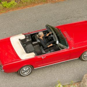 woman driving classic red mustang convertible