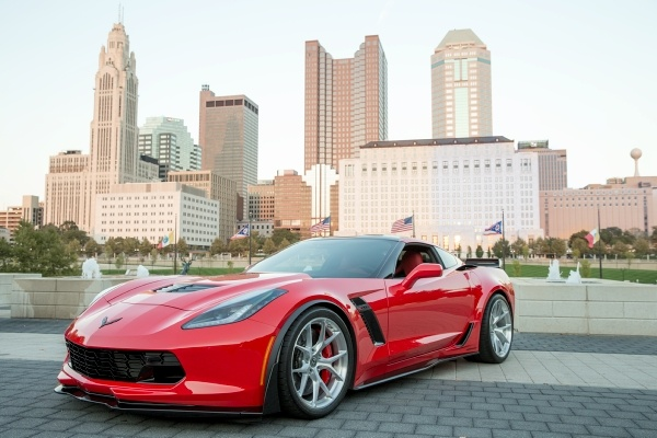 red sports car in front of city skyline