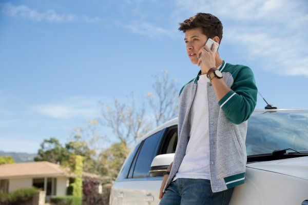 man on cell phone leaning on car