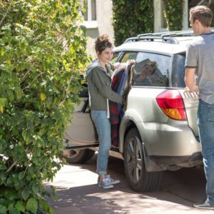 teenage boy and girl loading a white station wagon