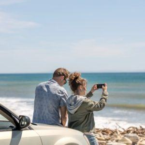 couple standing by car taking a photo of the ocean