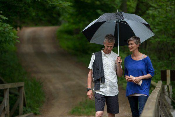 couple walking holding umbrella