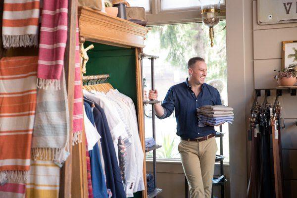Man in clothing store holding folded khaki pants