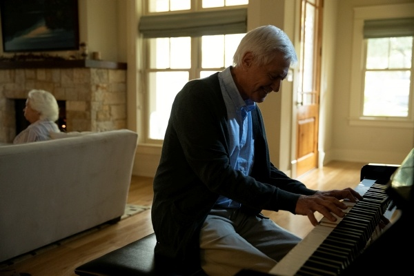 elderly man playing a piano