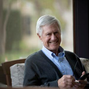 man in sweater smiling and using cell phone