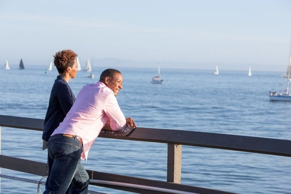 two people looking out into the ocean from a pier